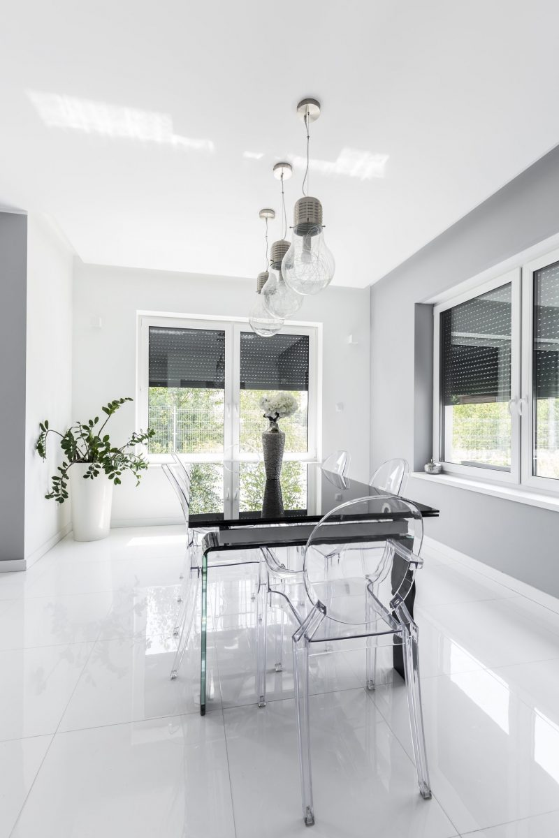 Minimalist modern dining room designed in white with black table and transparent chairs