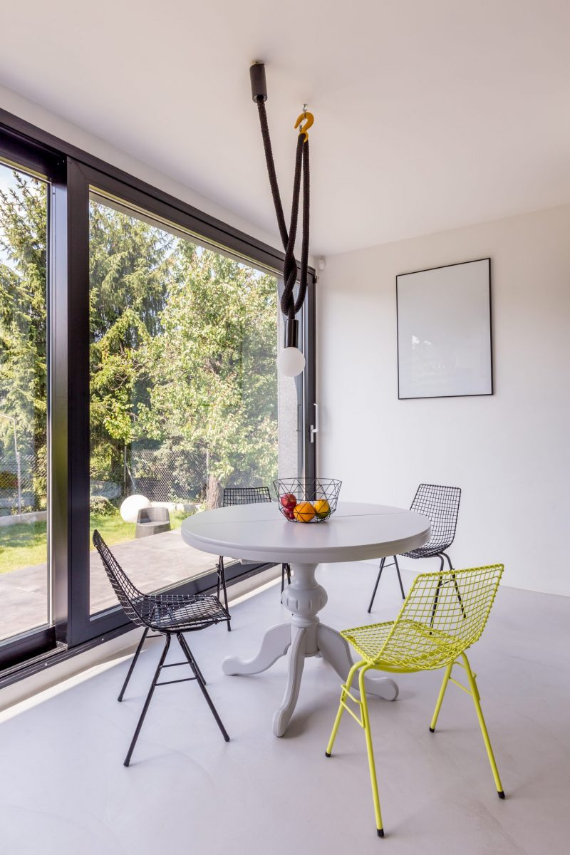 Round table and metal chairs in small stylish dining room with panoramic window